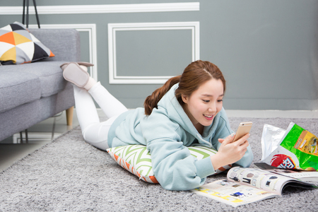 Young female Asian in pajamas reading books with snack on living room floor