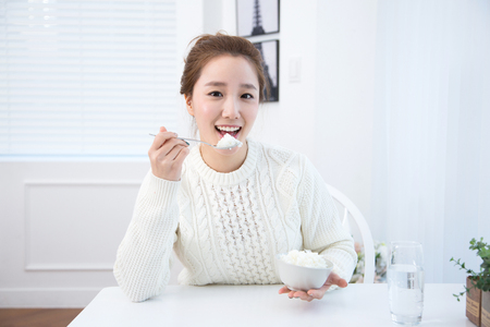 Young female Asian eating a bowl of rice in white interior room