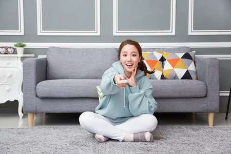 Young female Asian in pajamas watching TV in the living room/Tvroom