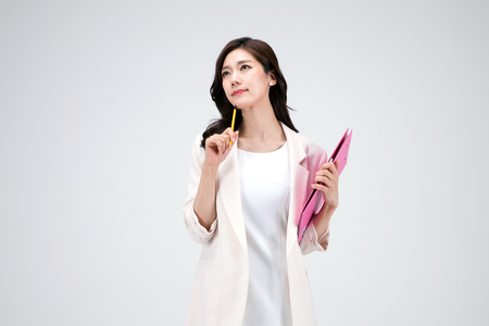 Isolated shot in studio - Asian career woman in white dress holding a file folder