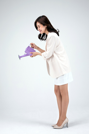 Isolated shot in studio - Asian career woman in white dress posing with water can