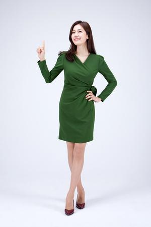 Lokalisierter Schuss im Studio - asiatische Karrierefrau im grünen Kleid, das mit Handzeichen aufwirft