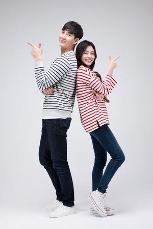 Tiro aislado en estudio - pareja asiática joven que presenta las camisetas presenta juntos Foto de archivo - 84545183