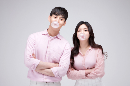 Isolated shot in studio - Asian young couple wearing matching outfits blowing bubble gum Stock Photo
