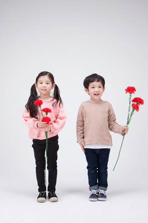 Isolated shot in studio - little Asian girl and boy posing with flower props