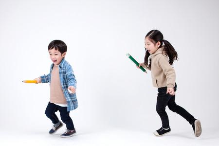 Geïsoleerde schot in de studio - kleine Aziatische meisje en jongen poseren met verschillende rekwisieten