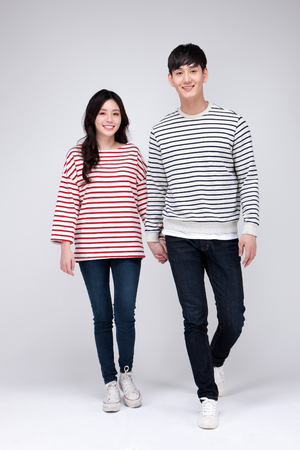Isolated shot in studio - Asian young couple wearing matching shirts in walking motion Stock Photo