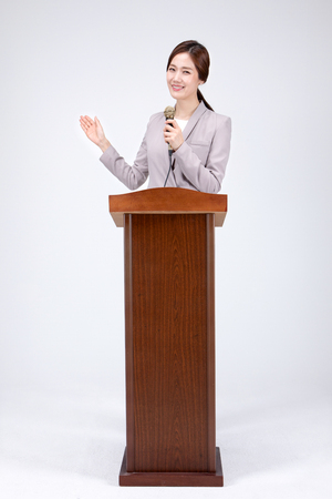 Isolated shot in studio - Asian career woman posing with a mic at podium
