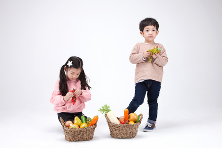 prank: Isolated shot in studio - little Asian girl and boy posing with a basket of vegetablesfruits props