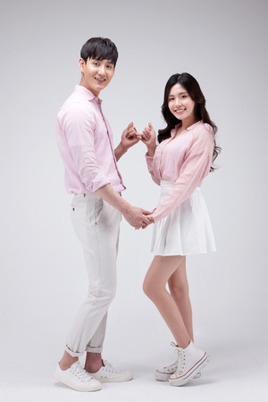 Isolated shot in studio - Asian young couple wearing matching outfits posing together