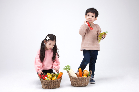 Isolated shot in studio - little Asian girl and boy posing with a basket of vegetablesfruits props