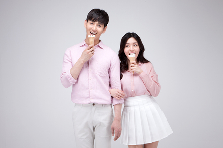 Isolated shot in studio - Asian young couple wearing matching outfits posing with ice cream