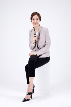 Isolated shot in studio - Asian career woman in pants suit posing with a mic