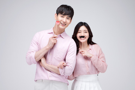 prank: Isolated shot in studio - Asian young couple wearing matching outfits posing with props