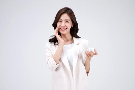 Geïsoleerde schot in studio - Aziatische carrièrevrouw in het witte kleding stellen met de producten van de huidzorg Stockfoto