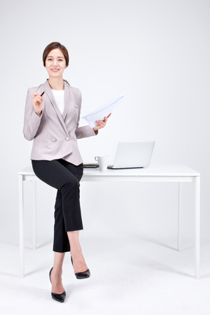 Isolated shot in studio - Asian career woman in pants suit sitting down on desk with a laptop Banco de Imagens