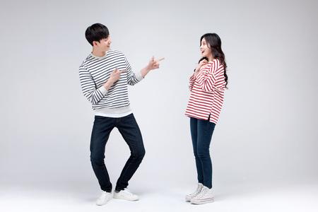 アジアの若いカップルが一緒にポーズ一致するシャツを着てスタジオに分離ショット