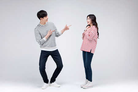Isolated shot in studio - Asian young couple wearing matching shirts posing together
