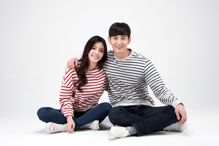 Isolated shot in studio - Asian young couple wearing matching shirts sitting down on the floor