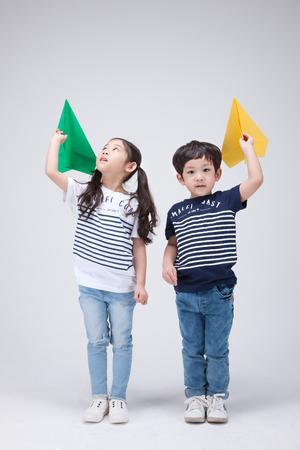 Disparo aislado en estudio - pequeña niña asiática y niño posando con diversos accesorios
