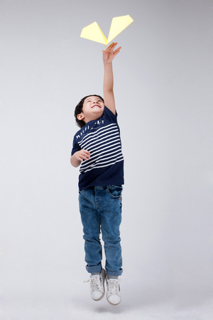 Isolated shot in studio - little Asian boy posing with various props