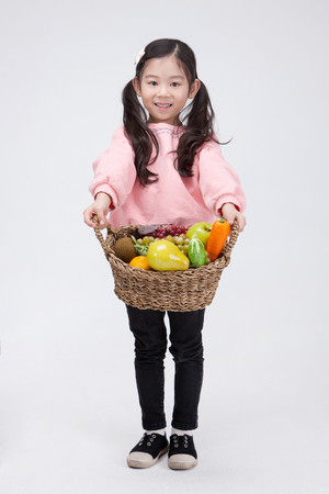 Isolated shot in studio - little Asian girl posing with a basket of vegetablesfruits props
