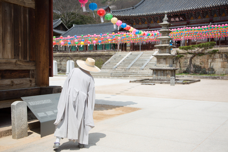 Buddhist temple in Korea - Monk wearing strat hat walking across the yard under the colorful lanterns Stock Photo