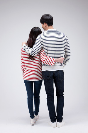 Isolated shot in studio - Back shot of Asian young couple wearing matching shirts in walking motion