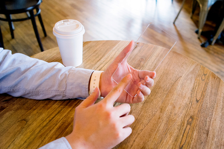 Isolated shot of hands holdinggrabbing and operatingusing transparent smart phone
