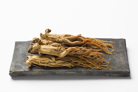 dried red ginseng,on korean traditional roof tile - isolated on white Zdjęcie Seryjne