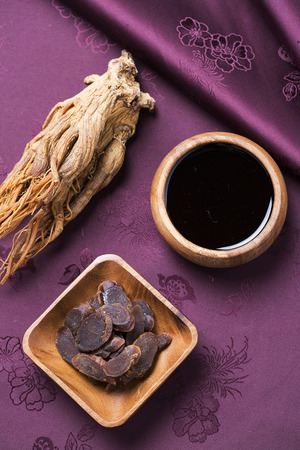 Honeyed red ginseng slices, dried red ginseng and red ginseng extract on Korean traditional silk Banco de Imagens
