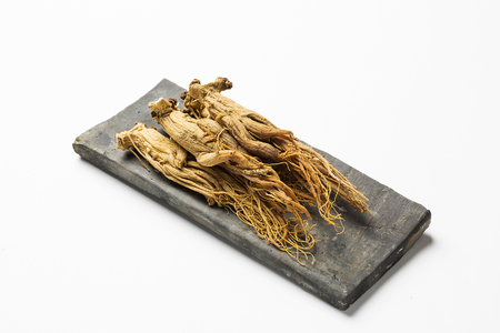 dried red ginseng,on korean traditional roof tile - isolated on white Stock fotó