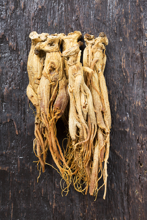 Dried red ginseng on wooden board