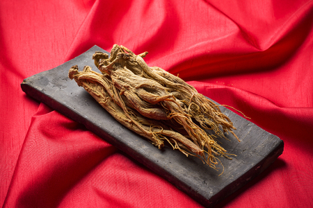 Dried red ginseng on red fabric