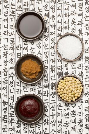 チョングッチャン (韓国高速発酵緑豆のペースト)、味噌 (韓国味噌)、塩、醤油、韓国紙に大豆 写真素材