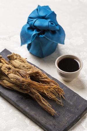 紅参は、韓国の伝統的なタイル、紅参エキス、青いシルクで包まれた贈り物を乾燥 写真素材