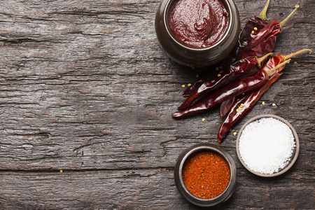 Dried dried red chillies, chilli powder, salt and Gochujang(Korean chilli paste) on wooden board