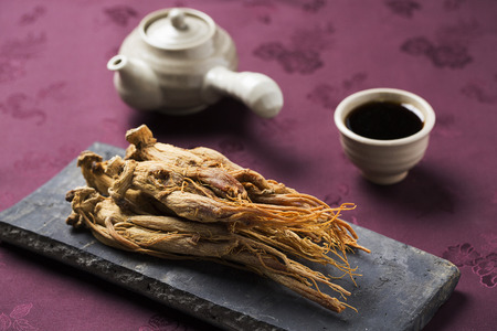 dried ginseng,on a Korean traditional roof tile and red ginseng extract