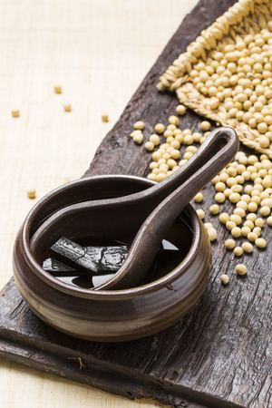 Soy sauce and soy beans on wooden board