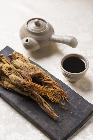 Dried red ginseng, red ginseng extract and Korean traditional teapot on Korean traditional silk