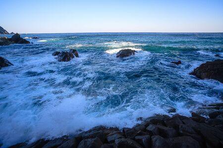 Golven breken het genereren van witte schuimen op rotsachtige kust Stockfoto