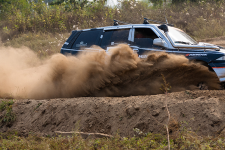 SUV car drifting on the dirt road as generating dirt wind