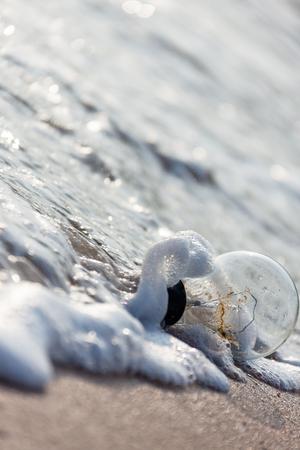 Abondoned lightbulb and sand beach