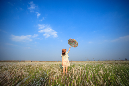 A girl holding an opened umbrella in the middle of reed field under the blue sky