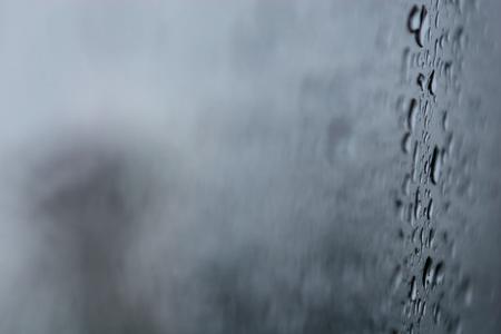 Close up shot of raindrops lingering on window