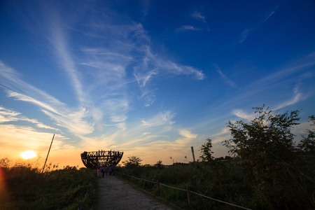 Scenery of reed field and hemisphere shape observation deck at sunset