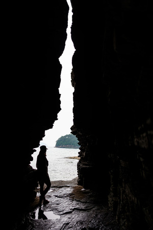 Silhouette of a girl posing for photoshoot as standing between rock cliffs