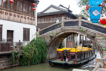Suzhou, China - A boat sailing on a canal between houses