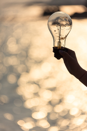 A hand holding a light bulb with background of ocean at sunset Stock Photo