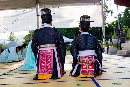 한국 다노제 - 한복에서 한국 사람이 제단에 꿇고있다.